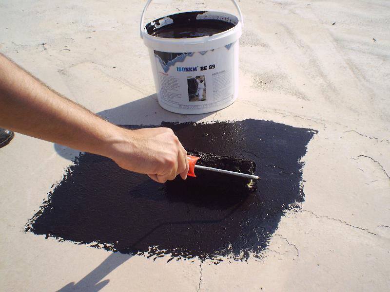 Bituminous (asphalt) paint being applied on a roof top crack