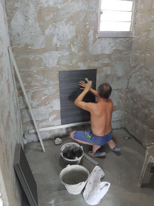 A contractor laying down a waterproofing tile on a building's dry wall of an unspecified room. He is shirtless.